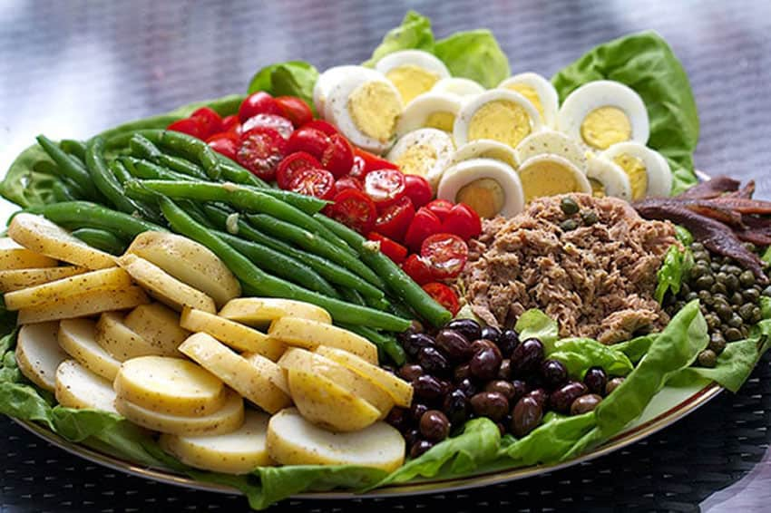 artfully arranged tuna nicoise salad on a platter with a row of sliced potatoes, green beans, cherry tomatoes, sliced hard-boiled eggs, a pile of tuna and a pile of olives