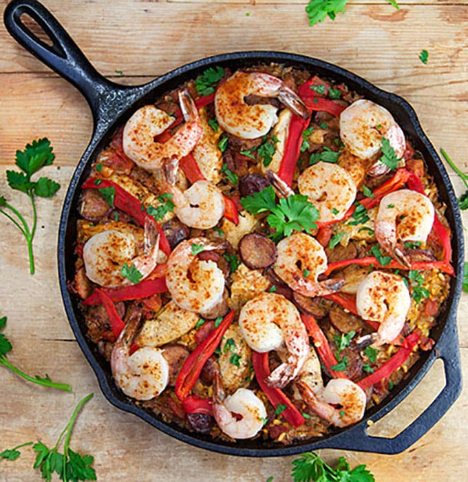 Cast iron skillet with paella showing shrimp, sausage, red peppers rice and parsley