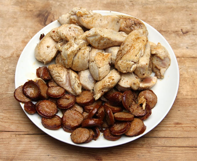 a white plate filled with sliced cooked sausages and chunks of cooked chicken breast