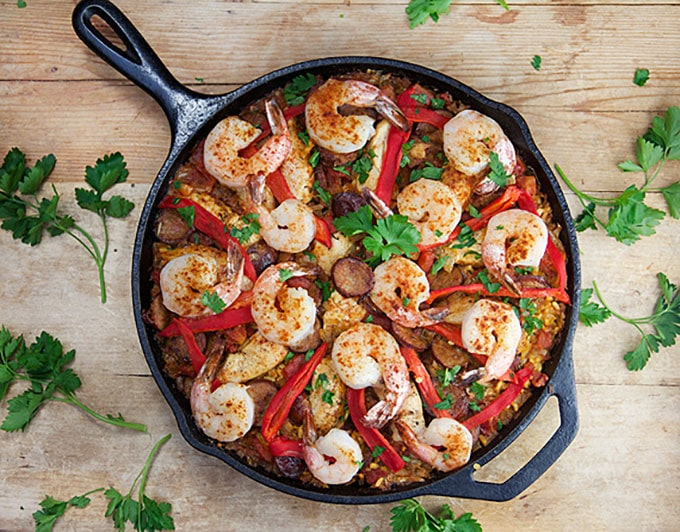 cast iron skillet filled with paella: saffron rice, spicy shrimp, slices of sausage and strips of red pepper. Lots of parsley for garnish.