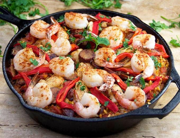 Cast iron skillet filled with chicken, shrimp and sausage paella.