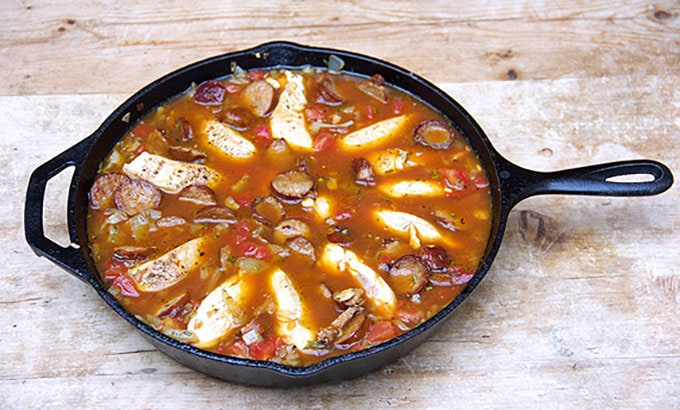 cast iron skillet filled with sausages, chicken and other ingredients for paella
