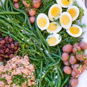 white platter topped with salad nicoise: tuna, small red potatoes, sliced hard boiled eggs, nicoise olives and French green beans
