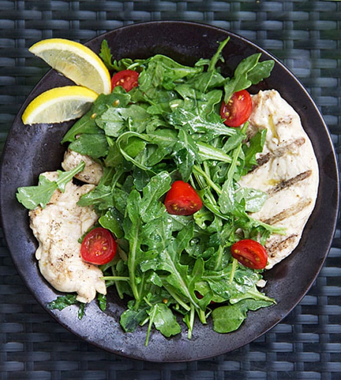 Chicken paillard is an Italian classic recipe that's easy and perfect for grilling season: thin scallops of chicken marinated in lemony dijon vinaigrette, grilled, and topped with arugula salad l www.panningtheglobe.com