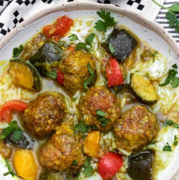 a bowl of Indian spiced lamb meatball stew with colorful ratatouille