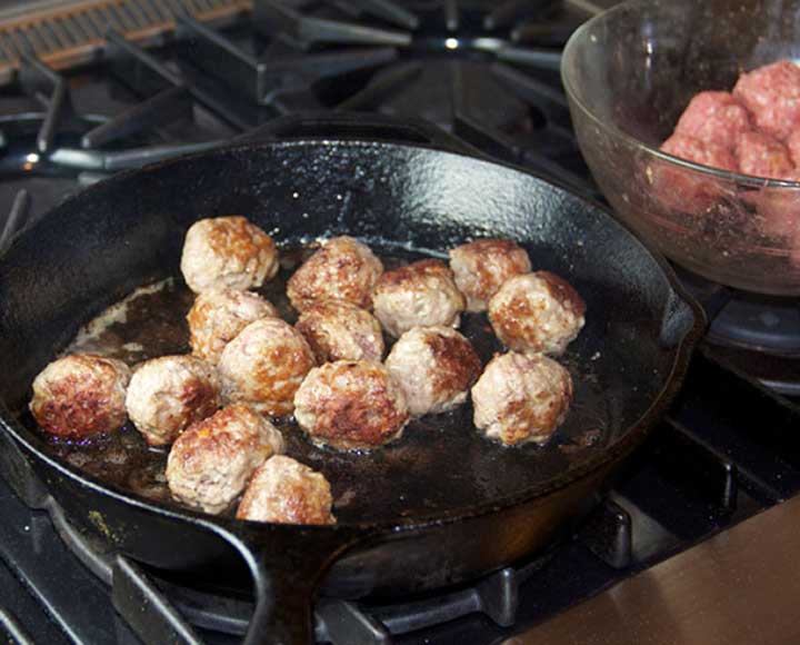 showing how to sauté lamb meatballs in a cast iron skillet to brown them