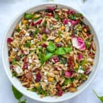 A white bowl filled with colorful orzo pasta salad and a sprig of basil in the middle
