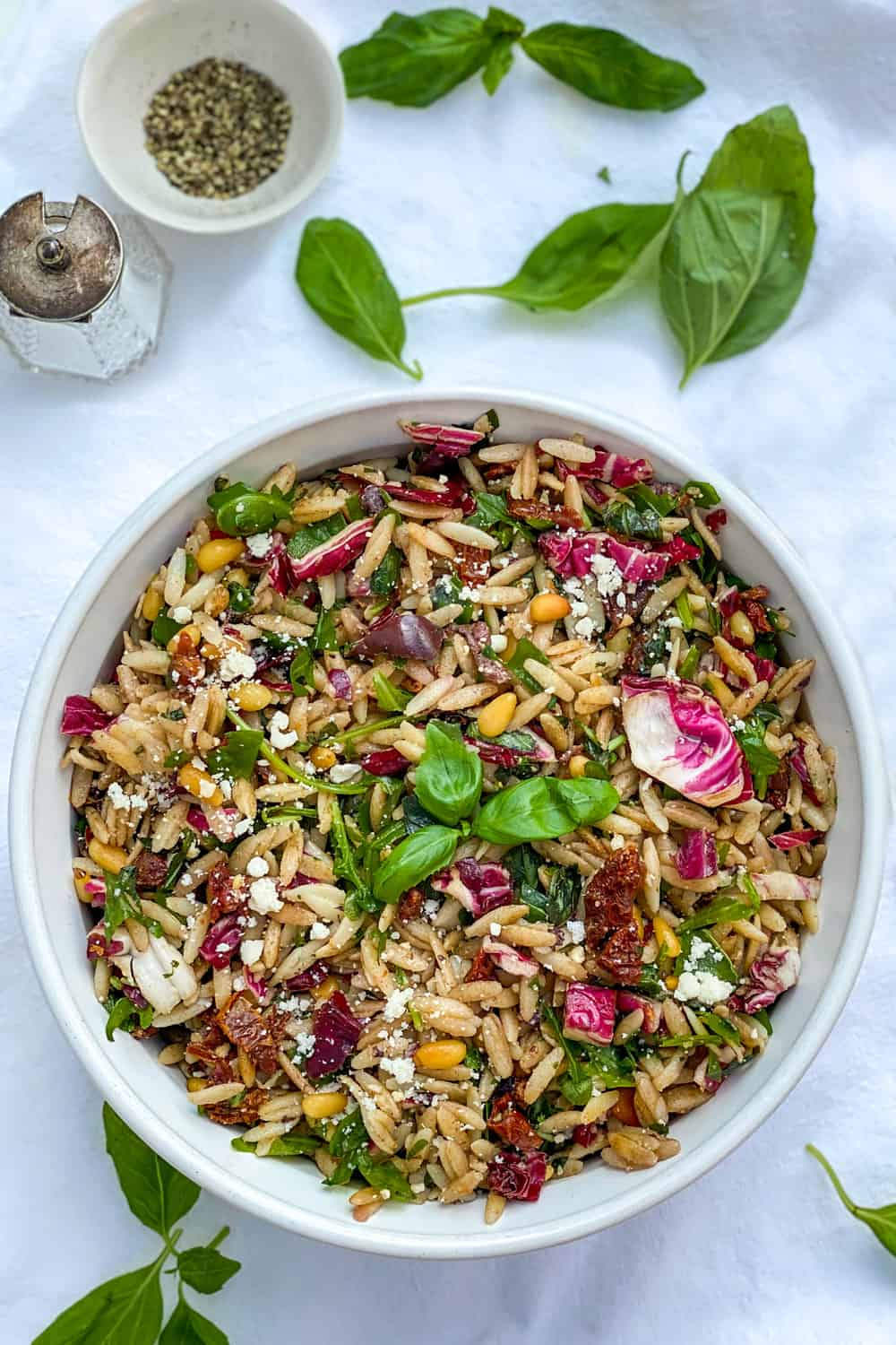 Bowl of orzo pasta salad on white tablecloth with basil leaves strewn around