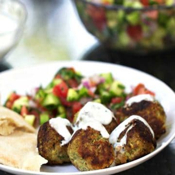 5 turkey falafel meatballs on a plate, drizzled with yogurt sauce