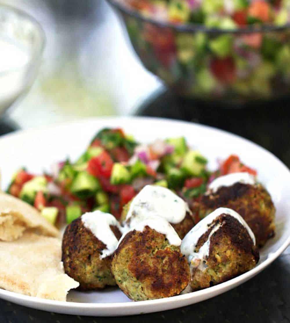 5 turkey falafel meatballs on a plate, drizzled with yogurt sauce