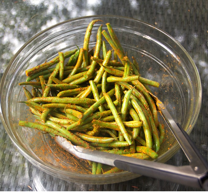 fresh green beans in a glass bowl with tongs, tossing the beans with Indonesian satay spices