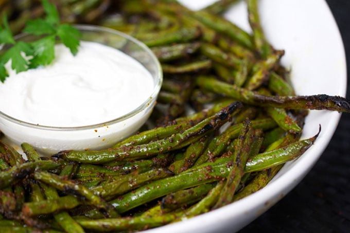 close up of grilled green beans and lemon aioli in a white bowl