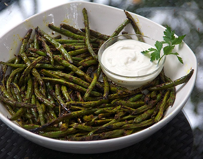 Spicy, flavorful, grilled green beans are an addictive healthy appetizer. Fresh green beans are tossed with homemade Indonesian satay spice mix and grilled. Serve with lemony, garlicky aioli to dip.