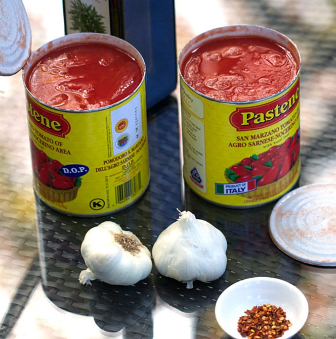 Ingredients for tomato sauce: cans of Italian plum tomatoes, bulbs of garlic.