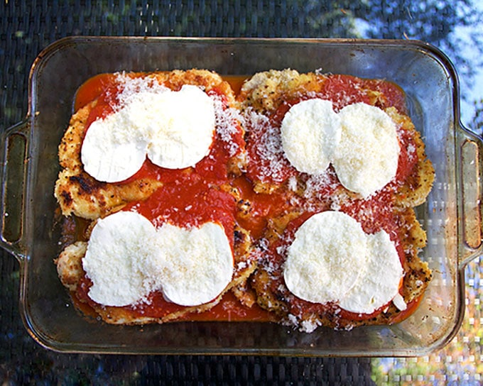 Glass baking pan with breaded chicken cutlets, tomato sauce and mozzarella cheese, showing How to make breaded chicken Parmesan