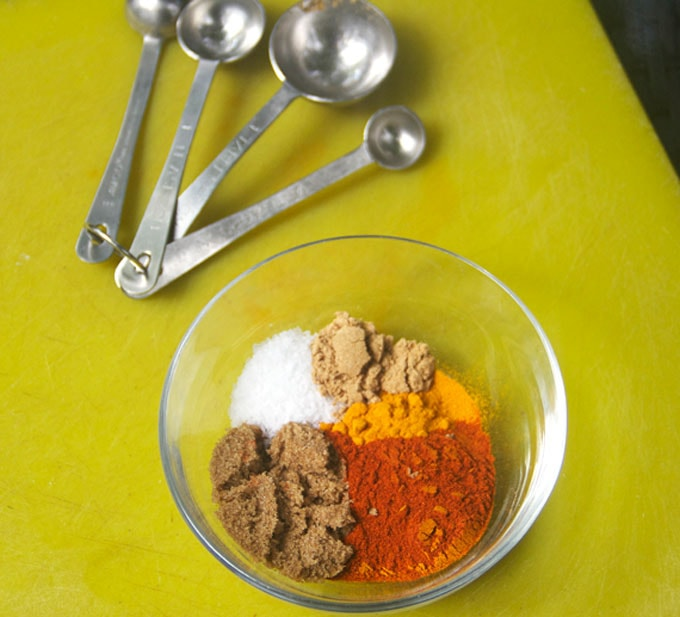 photo shows how to make Indonesian sate spice mix with give different spices in a bowl and measuring spoons.