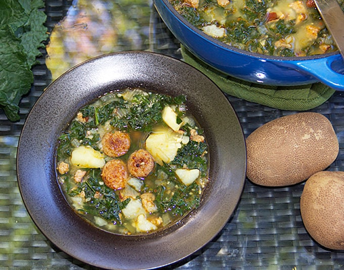 a bowl of sausage kale potato soup with a couple of russet potatoes o the side