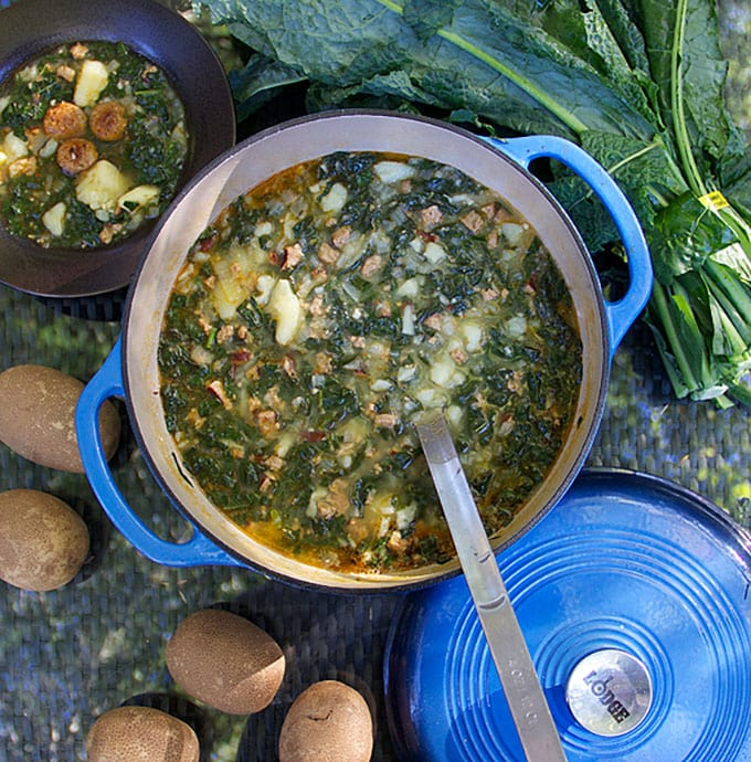a blue Dutch oven filled with Portuguese Sausage Kale Potato Soup