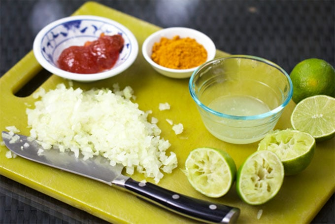 green cutting board topped with chopped onions, halved juiced limes, a small bowl of mango chutney, a small bowl of curry powder and a small bowl of lime juice