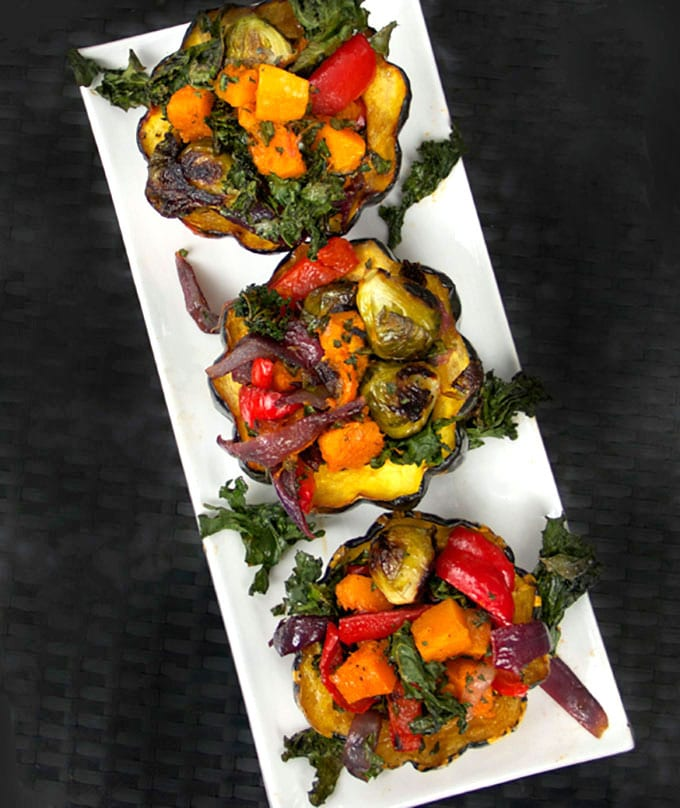three roasted squash halves stuffed with a rainbow of roasted vegetables