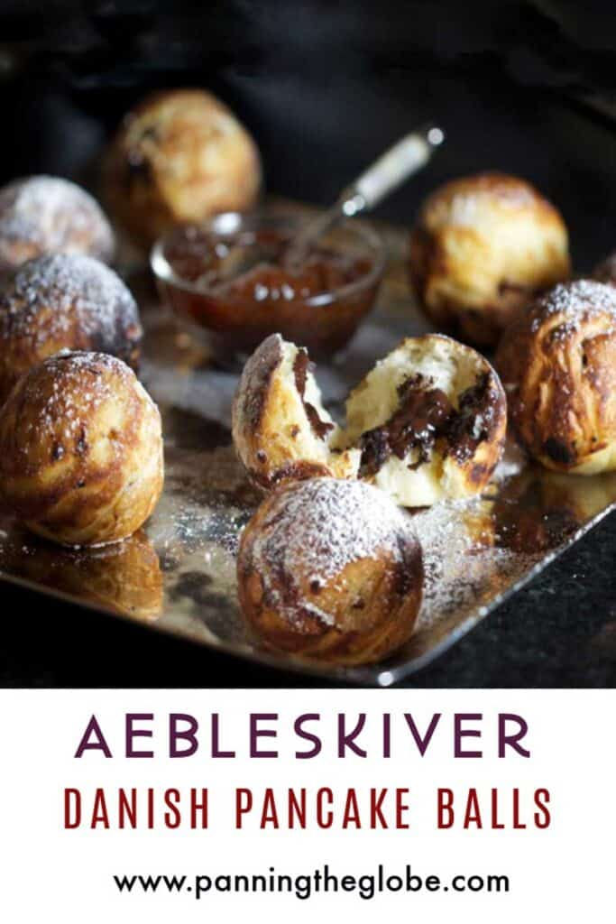 pinterest pin: silver platter topped with 8 aebleskiver pancakes and a little bowl of strawberry jam in the middle