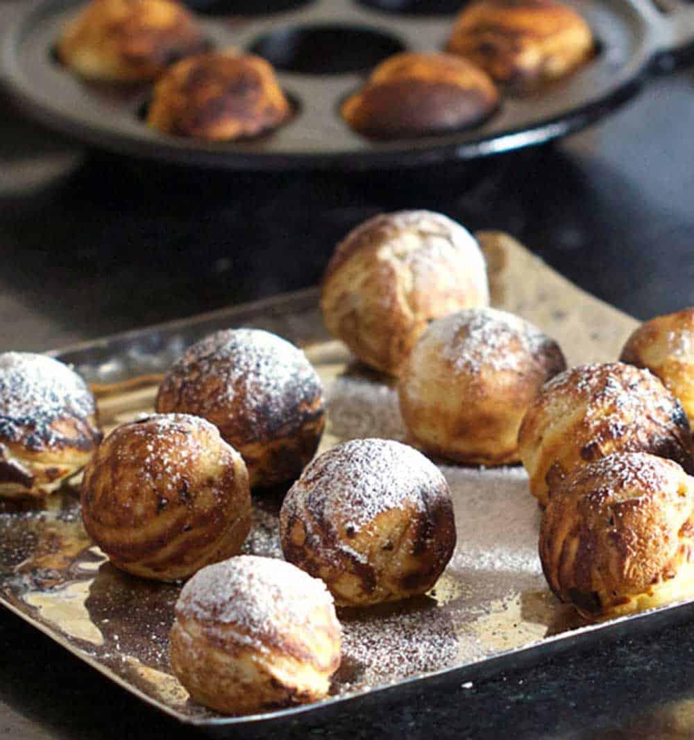 platter of Danish aebleskiver pancake balls sprinkled with powdered sugar