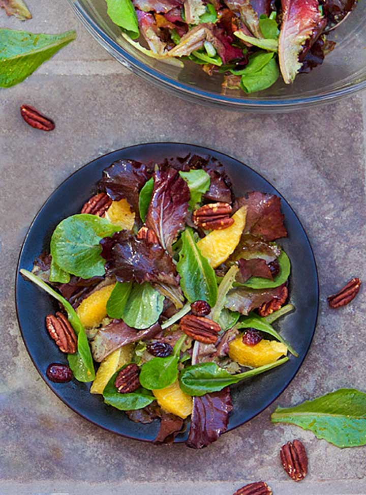 black plate topped with a salad of mixed baby greens, oranges, pecans and cranberries.