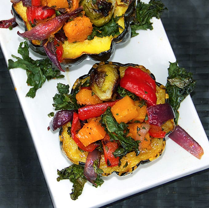 two roasted squash halves stuffed with a rainbow of roasted vegetables