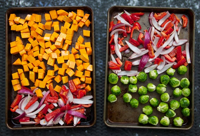 two rimmed baking sheets, one with cubed butternut squash, sliced onions and sliced red bell peppers, the other with Brussels sprouts and sliced red onions and sliced red peppers.