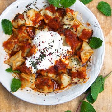 Turkish Manti is a dish for a special occasion: tiny lamb-stuffed dumplings topped with three sauces: caramelized tomato sauce, brown butter sauce, and garlicky yogurt sauce. This recipe shows you how to make authentic Turkish manti at home.