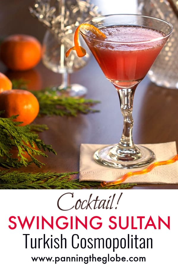 vibrant red swinging sultan cocktail in a martini glass surrounded by 3 oranges, sprigs of evergreen and crystal glassware