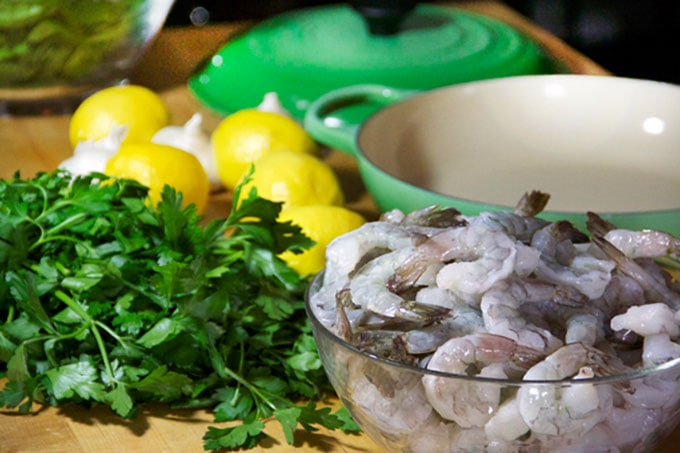 Raw shrimp in a bowl with lemons and parsley