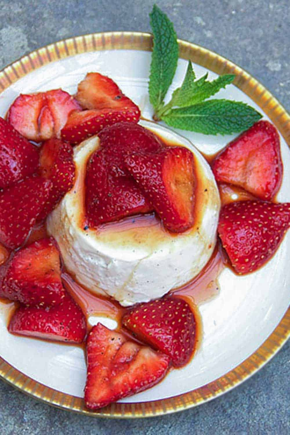 vanilla panna cotta surrounded by and topped with balsamic marinated strawberries