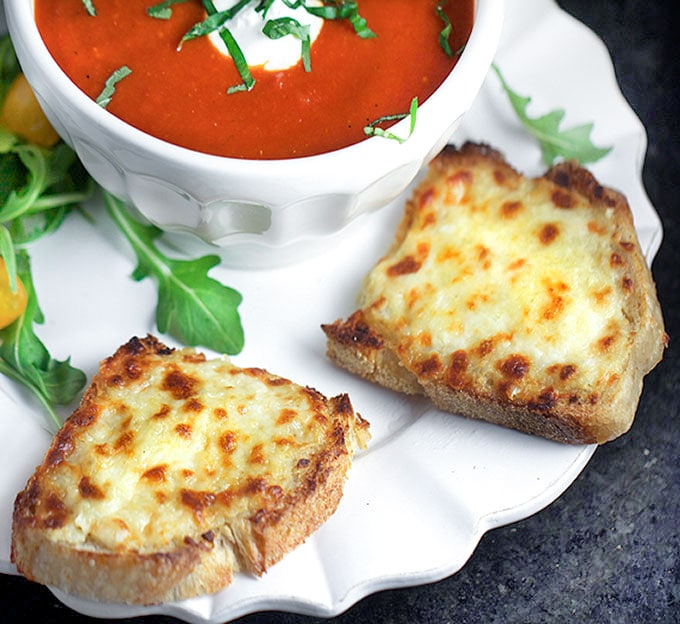 Open faced grilled cheese sandwiches with a bowl of tomato soup