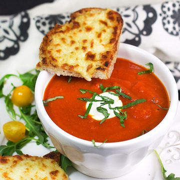 Grilled cheese and tomato soup is the ultimate comfort food pairing and the perfect lunch combo. Here's a special recipe for delicious spiced-up tomato soup and open-face oven grilled cheese with some secret ingredients that make it extra tasty.