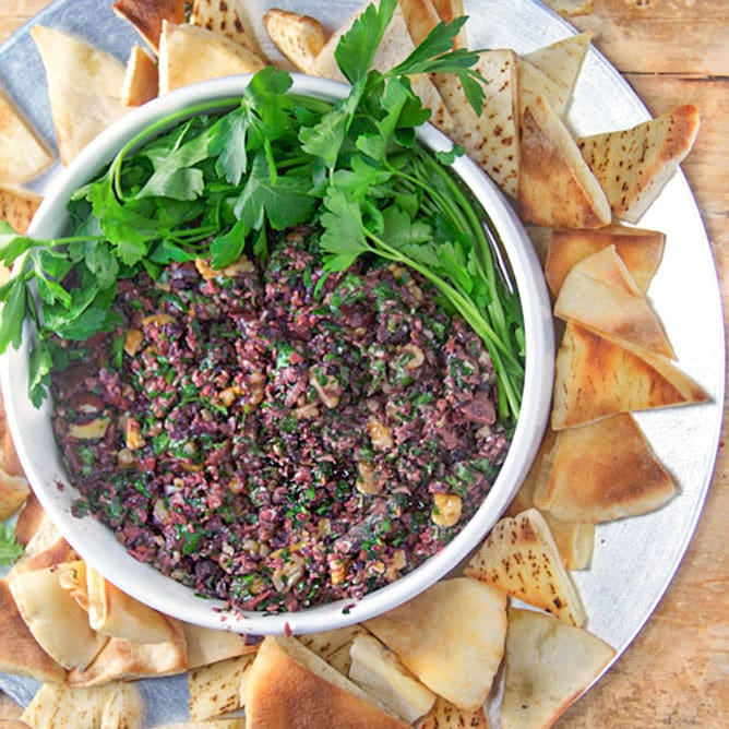 a bowl of spicy Turkish tapenade surrounded by pita triangles and topped with parsley
