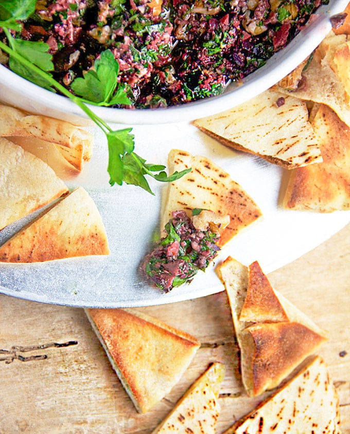 spicy turkish tapenade in a bowl surrounded by toasted pita triangles