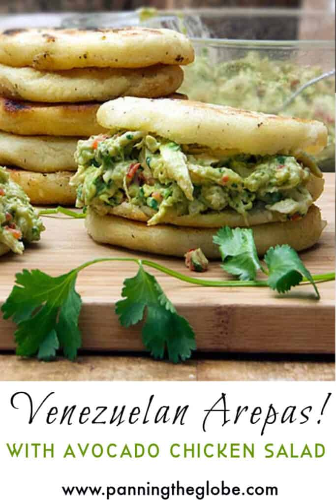 an arepa stuffed with avocado chicken salad and a stack of arepas in the background