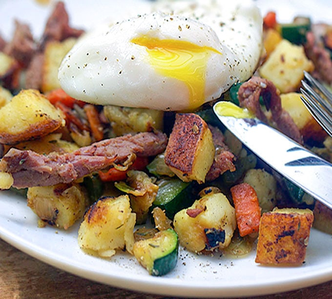 Corned beef hash with lots of veggies and a runny poached egg on top