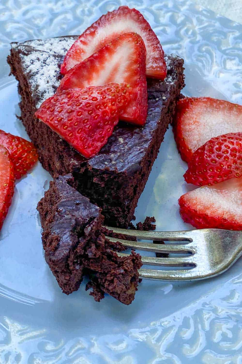 Slice of bittersweet flourless chocolate truffle cake on on a light blue plate with a fork sticking into one bite of cake and some sliced strawberries on the side