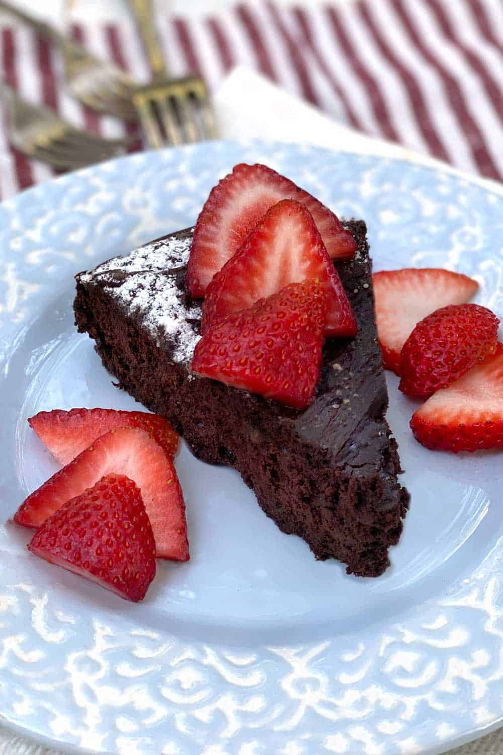 slice of flourless chocolate truffle cake on a light blue plate with sliced strawberries on top and on the sides