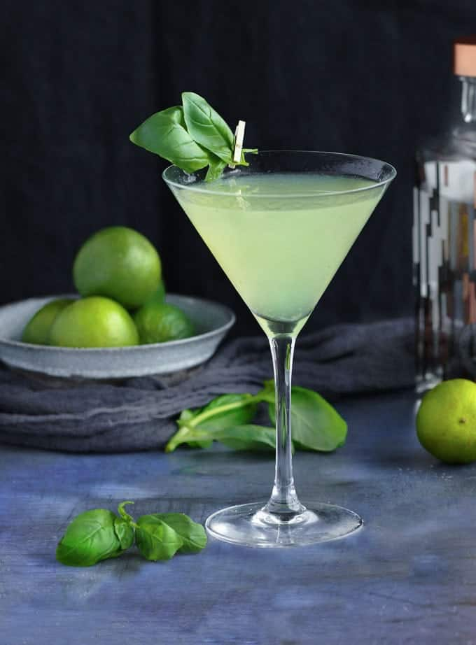 martini glass filled with a light green drink called a basil dazzle, with a spring of basil attached to the glass with a tiny clothespin and a bowl of limes in the background