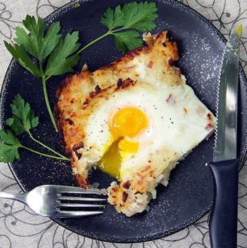 swiww rosti shredded potato casserole with soft cooked egg on top and a fork