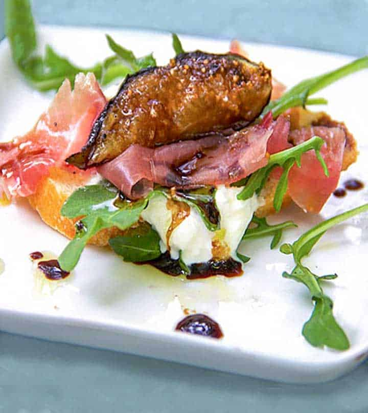 one piece of grilled fig, prosciutto and burrata bruschetta, on a small square white plate