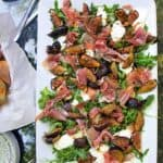 white rectangular platter topped with grilled figs, prosciutto and burrata and arugula