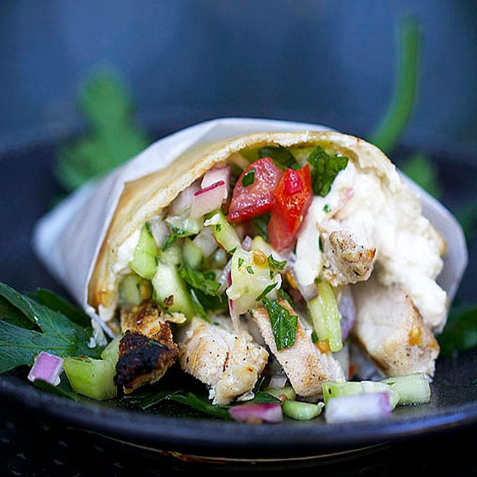 A roll up of chicken shawarma with lemony tahini sauce.