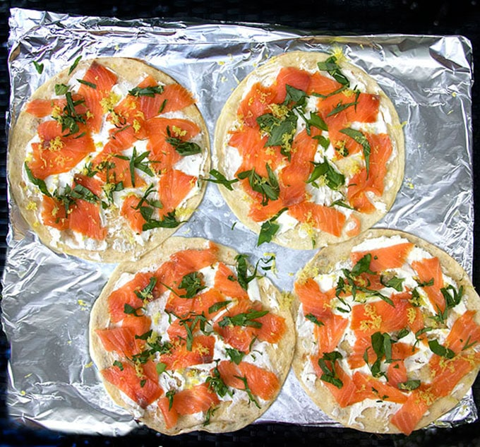 four flour tortillas on a foil-lined baking sheet, topped with goat cheese, smoked salmon, slivered basil and lemon zest