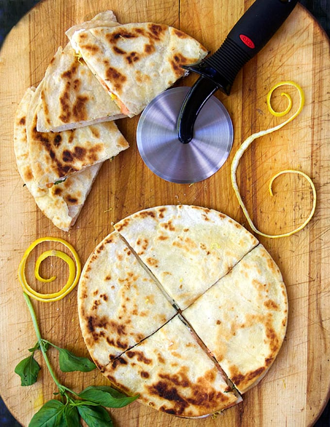 wooden cutting board topped with flour tortilla quesadillas cut into quarters, a pizza cutter, and some swirls of lemon peel