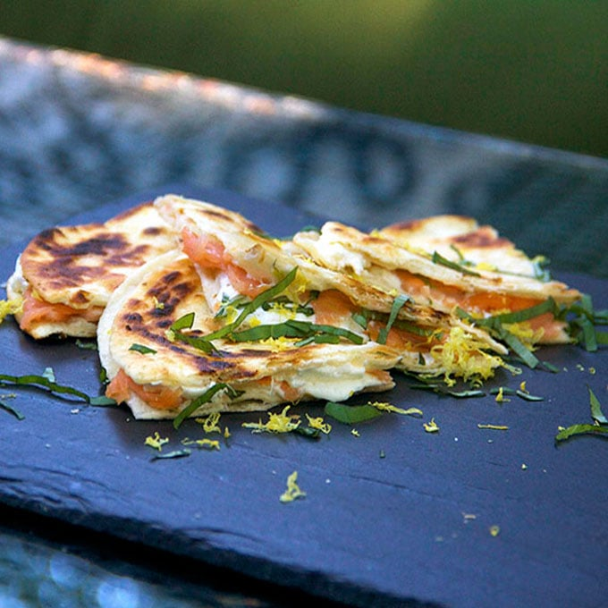 slate serving board topped with three triangular slices of smoked salmon quesadillas with goat cheese, lemon zest and slivered basil.