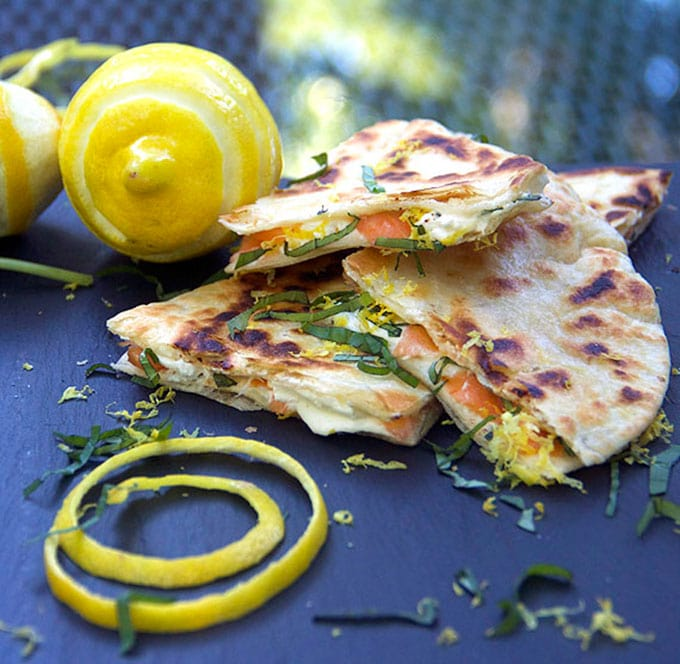 triangles of smoked salmon quesadillas with goat cheese with a coil of lemon peel on and a zested lemon and a confetti of slivered basil and lemon zest